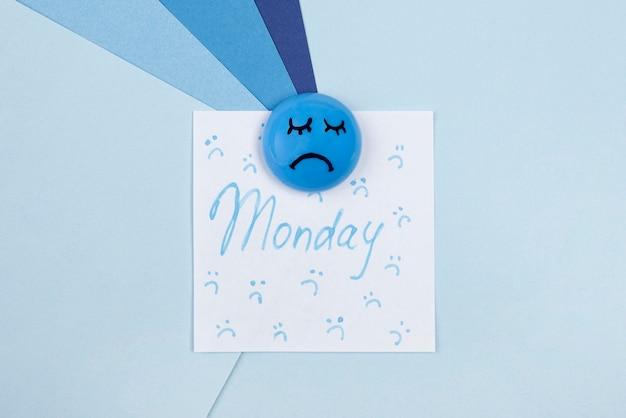 Vista superior de la cara triste con nota adhesiva para el lunes azul