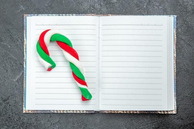 Vista superior de un caramelo de navidad en el cuaderno abierto sobre fondo oscuro