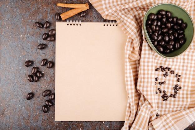 Vista superior de caramelo de nuez de chocolate glaseado en un tazón y cuaderno de bocetos sobre fondo negro
