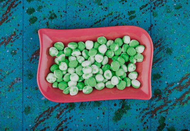 Vista superior de caramelos de azúcar verde en una bandeja de cerámica sobre fondo azul.