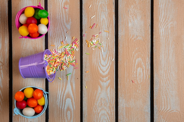 Vista superior de caramelos y chispitas de colores dispersos de un pequeño cubo