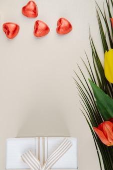 Vista superior de caramelos de chocolate en forma de corazón envueltos en papel rojo, caja de regalo y un ramo de tulipanes de colores en la mesa blanca con espacio de copia