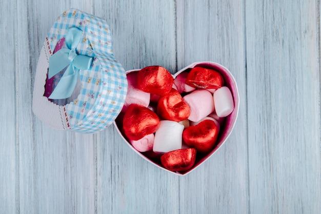 Vista superior de caramelos de chocolate en forma de corazón envueltos en papel rojo con malvavisco rosa en una caja de regalo en forma de corazón sobre una mesa de madera gris