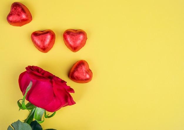 Vista superior de caramelos de chocolate en forma de corazón envueltos en papel rojo con rosa roja sobre mesa amarilla con espacio de copia