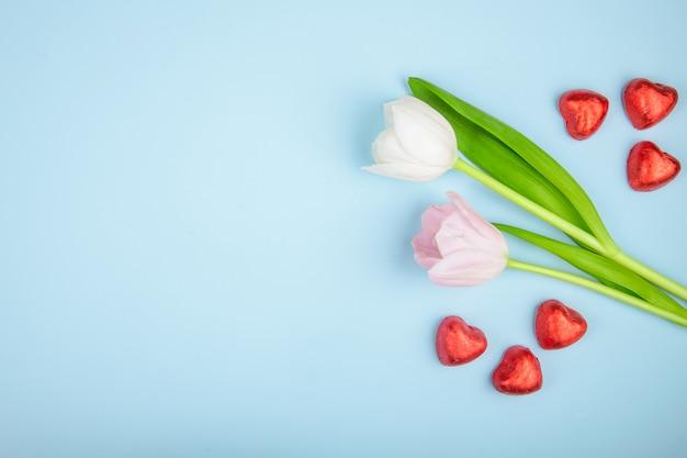 Vista superior de caramelos de chocolate en forma de corazón en papel rojo con tulipanes de color rosa en la mesa azul con espacio de copia