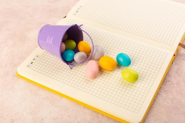 Una vista superior de los caramelos de colores en el cuaderno y el escritorio de color rosa caramelo dulce bombón golosina