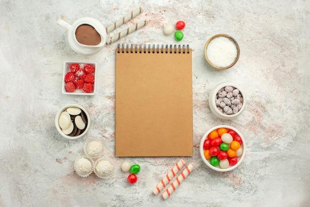 Vista superior de caramelos de colores con galletas sobre fondo blanco pastel de té de galletas de arco iris de color