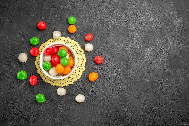 Vista superior de caramelos de colores sobre fondo oscuro color arco iris dulce té