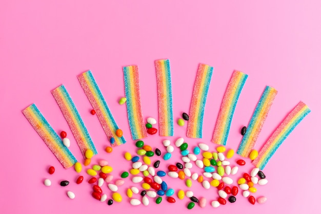 Una vista superior de caramelos coloridos con mermeladas de arco iris en el escritorio rosa, arco iris de azúcar dulce