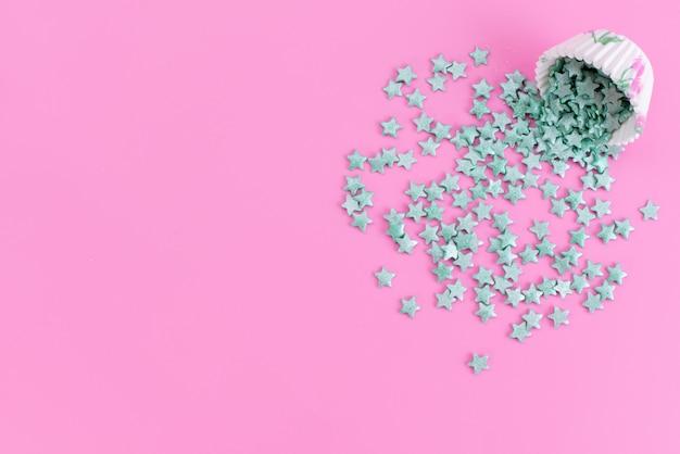Una vista superior de caramelos de estrella en forma de caramelos verdes en el escritorio rosa, estrella dulce de azúcar de color