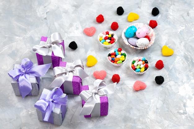 Una vista superior de caramelos multicolores dentro de pequeños platos junto con mermeladas en forma de corazón y cajas de regalo de color púrpura en el arco iris de celebración de azúcar de cumpleaños de fondo gris