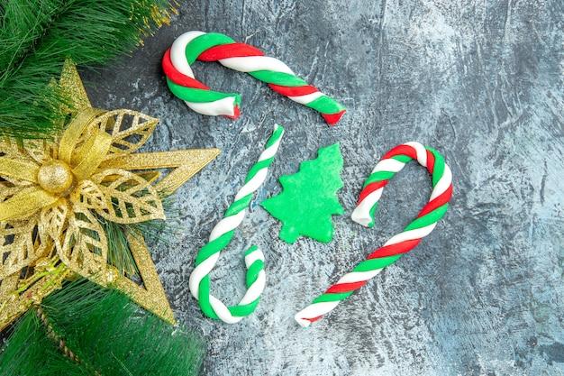 Vista superior de caramelos de navidad adornos de navidad en superficie gris