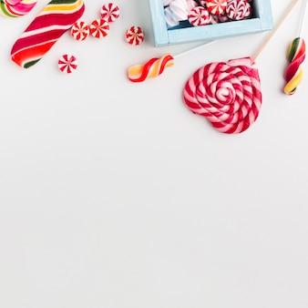 Vista superior de caramelos y piruletas con espacio de copia