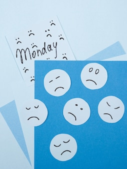 Vista superior de caras tristes para el lunes azul con nota adhesiva