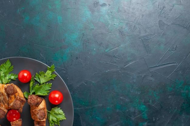 Vista superior de la carne cocida en rodajas con tomates cherry verdes dentro de la placa sobre el fondo azul oscuro