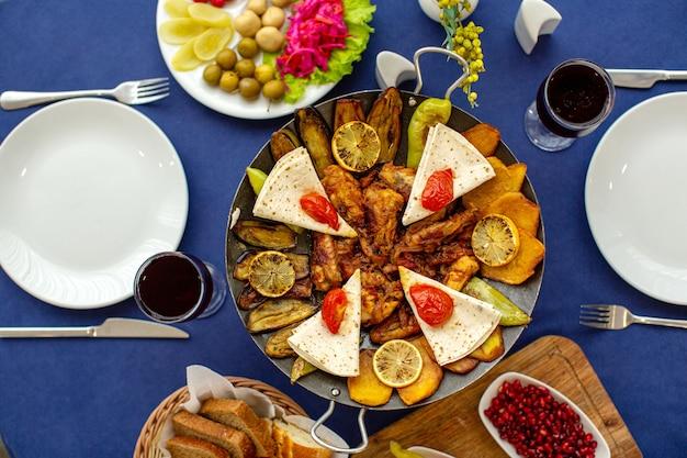 Una vista superior de carne cocinada junto con granada y verduras frescas con rebanadas de pan sobre la mesa azul