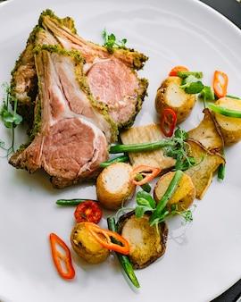 Vista superior de carne en costillas con papas, champiñones y judías verdes