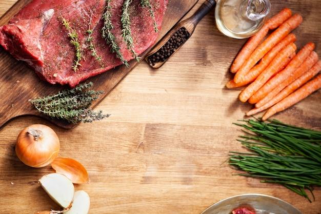 Vista superior de carne cruda e ingredientes saludables para barbacoa en mesa de madera. verduras sabrosas. alimentos orgánicos.