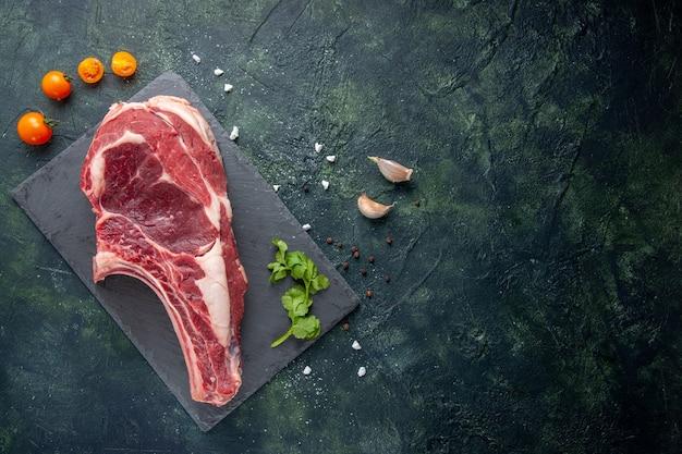 Vista superior de la carne cruda grande rebanada de carne en la superficie oscura