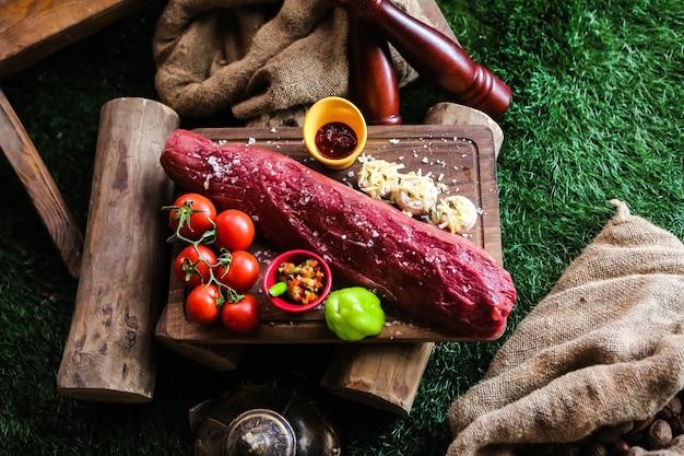 Vista superior carne cruda con tomates champiñones con queso pimiento y especias en una bandeja