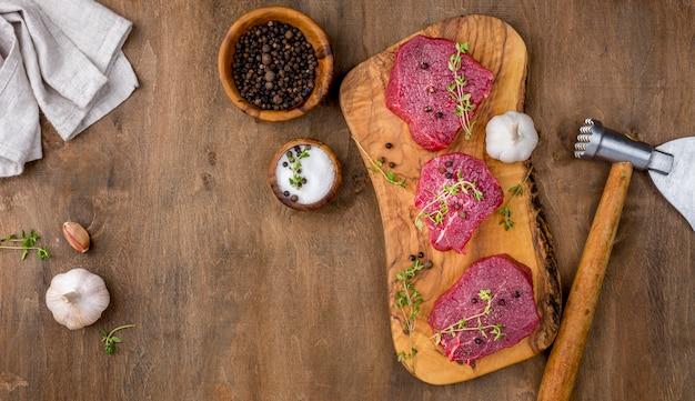 Vista superior de carne con especias y ajo.