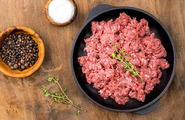 Vista superior de carne con especias y hierbas.