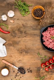 Vista superior de carne con especias y tomates.