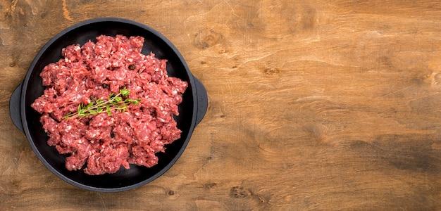 Vista superior de carne con hierbas y espacio de copia