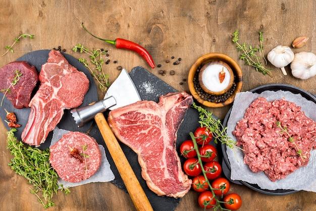 Vista superior de carne con hierbas y tomates.