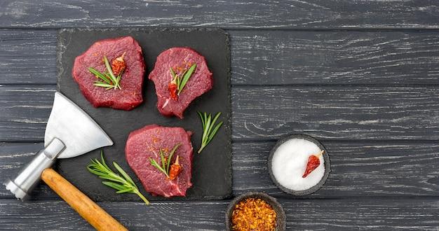 Vista superior de carne en pizarra con hierbas