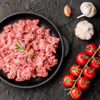 Vista superior de carne en plato con ajo y tomates