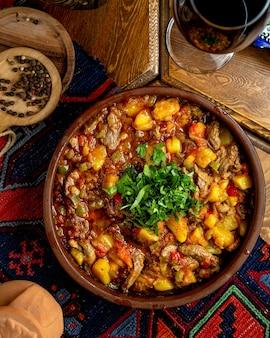 Vista superior de carne de res guisada con papas, pappers verdes y hierbas en un recipiente de arcilla sobre una mesa de madera