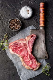 Vista superior de carne con sal y especias en pizarra