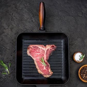 Vista superior de carne en sartén con especias y hierbas