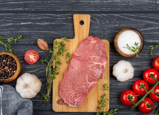 Vista superior de carne con tomate y ajo.