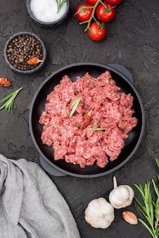 Vista superior de carne con tomate y especias.
