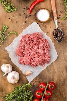Vista superior de carne con tomate y hierbas.