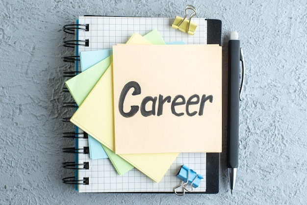 Vista superior carrera nota escrita con pegatinas y bloc de notas en la superficie blanca oficina de trabajo cuaderno escolar sueldo colegio color de negocios