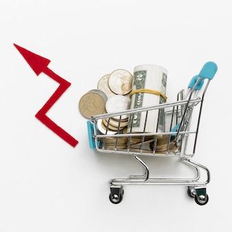 Vista superior carrito de compras lleno de dinero