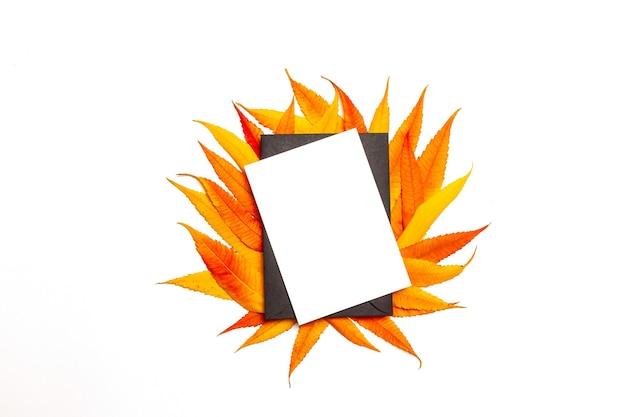 Vista superior de la carta en blanco de la maqueta o postal en sobre negro con hojas amarillas y rojas otoñales