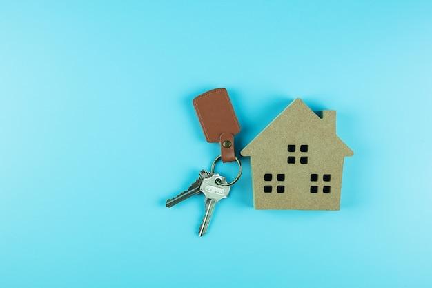 Vista superior de la casa modelo y llave. conceptos bancarios, inmobiliarios, de inversión, financieros y de ahorro.