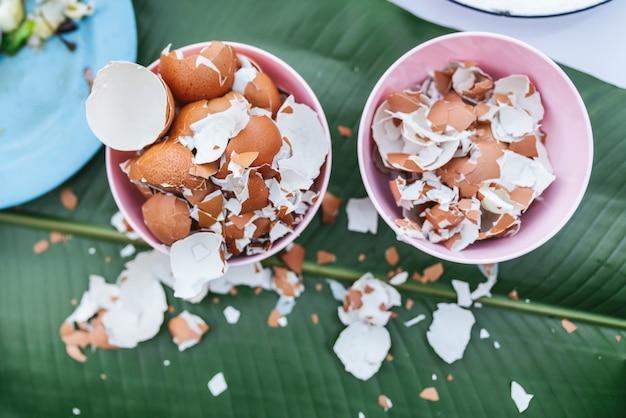 Vista superior de cáscaras de huevo cocido en un tazón pequeño sobre hojas de plátano sobre la mesa