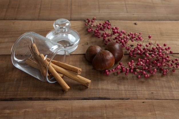 Vista superior de castañas y canela, manzanas, pimienta rosa, sobre una madera
