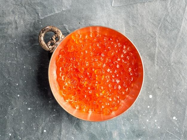 Vista superior del caviar rojo o endecha plana. tazón de caviar rojo en textura gris