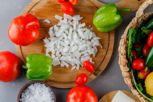 Vista superior de cebolla picada en tabla de cortar con tomate, sal, pimiento verde sobre superficie gris