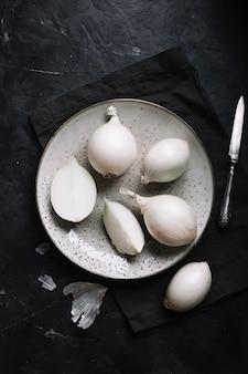 Vista superior de cebollas blancas con un cuchillo