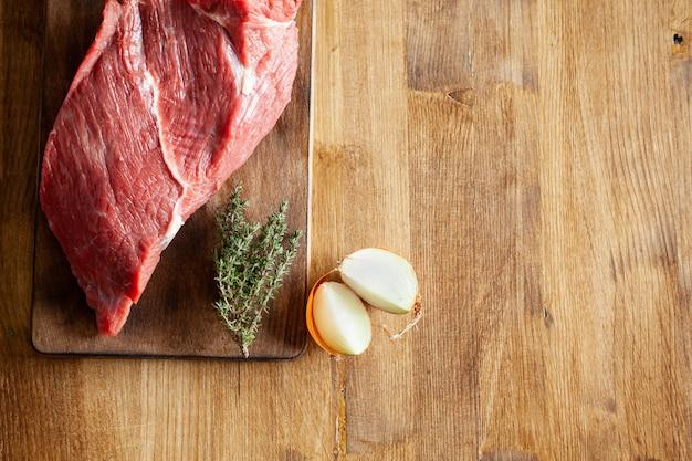 Vista superior de cebollas blancas junto a un gran trozo de carne roja en la mesa de madera. copie el espacio disponible.