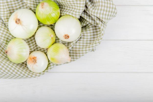 Vista superior de cebollas blancas sobre tela escocesa y fondo de madera con espacio de copia