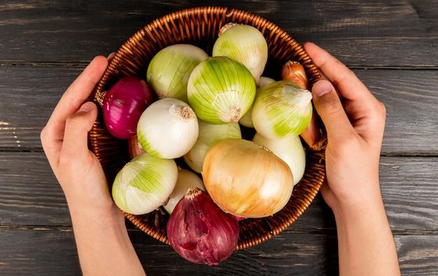 Vista superior de cebollas como chalota blanca roja y dulces en la cesta y las manos sosteniendo la cesta sobre fondo de madera