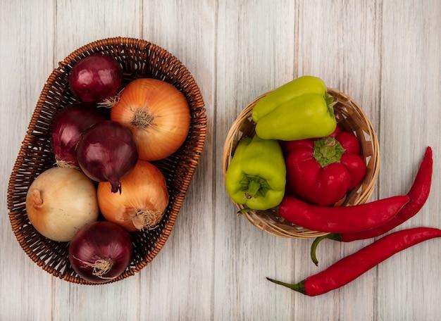 Vista superior de cebollas frescas y saludables en un balde con bell y chiles en un balde sobre un fondo de madera gris